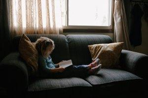 nena llegint al sofà